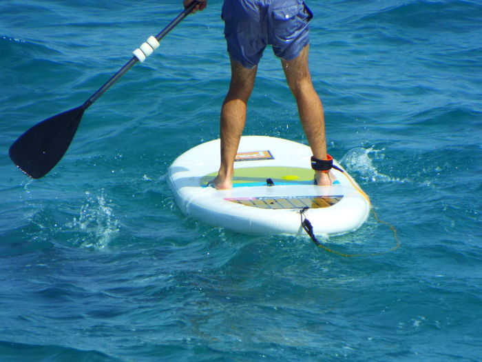 Low Section Of Man Paddleboarding