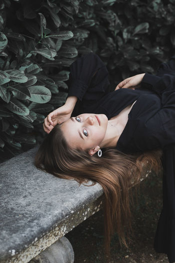 Portrait of woman lying on land by plants