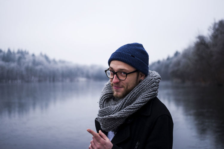Portrait of young man standing against lake and sky during winter