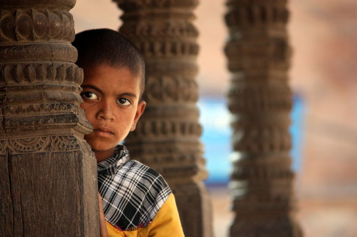 Observing - This photo was taken at one of the entrances of Bhaktapur, Nepal. From behind a pillar the boy was observing the tourists who entered the city. Bhaktapur Boy Children's Portraits Face Focus On Foreground Nepal Observing Observing The World Pillars Portrait My Favorite Photo Natural Light Portrait People And Places Resist Focus On The Story
