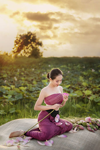 Woman holding water lily while sitting on plastic sack