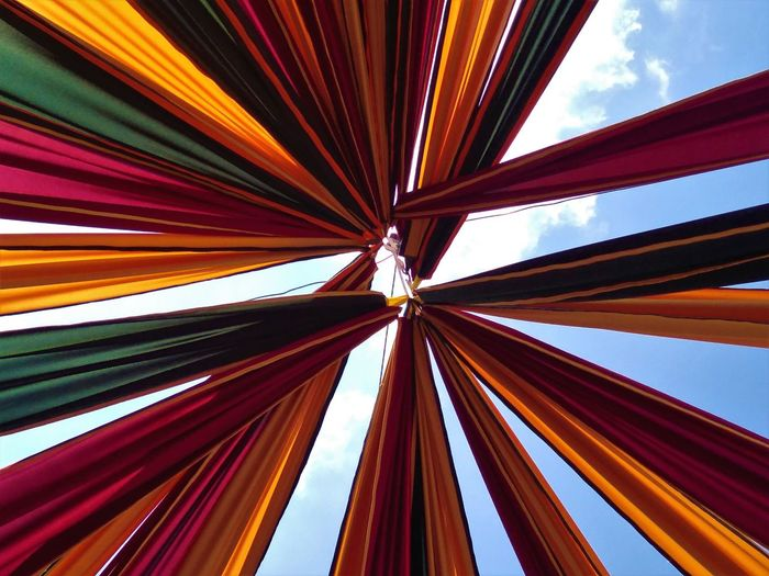 Low angle view of multi colored fabric against sky