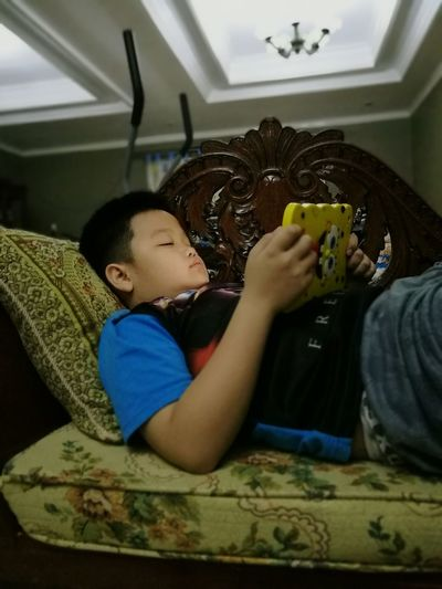 Mobile Conversations Indoors  Digital Native Child One Boy Only Rest & Relax Long Distance  Communication Funny Covers Keep In Touch  Domestic Life After School Past Time Loungingaround Comfortable