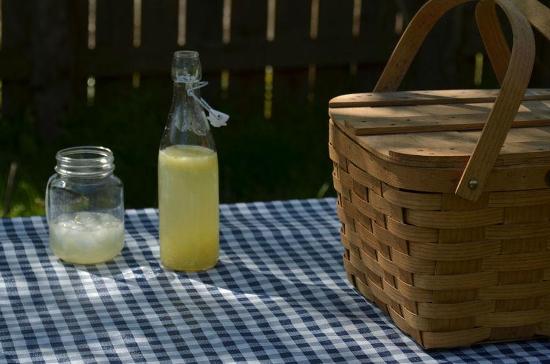 Vintage picnic basket, blue checked table cloth, bottles of lemonade and drinking jar glasses