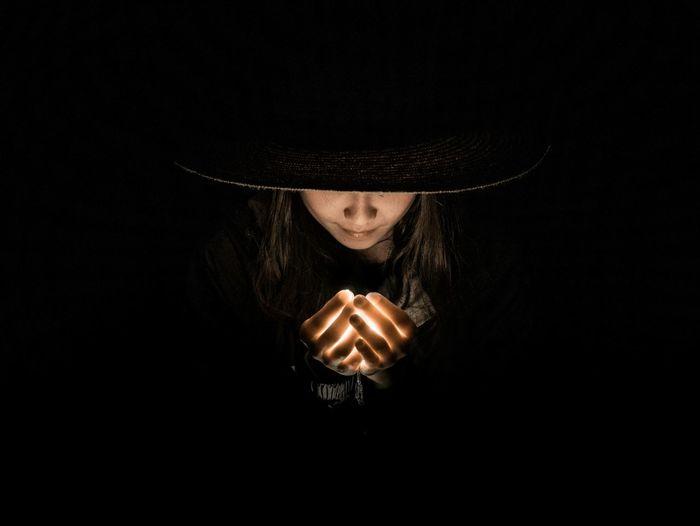 Portrait of woman holding hat against black background