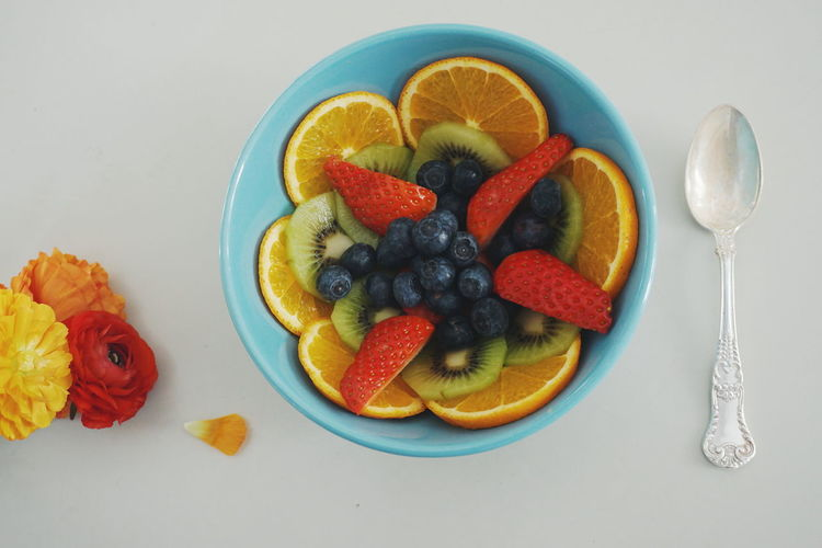 A Blue bowl with varity of fruits and berries Berry Fruit Blueberry Close-up Directly Above Flowers Food Food And Drink Fork Freshness Fruit Healthy Eating High Angle View Indoors  Kiwi - Fruit No People Plate Raspberry Ready-to-eat SLICE Spring Strawberry Table White Background