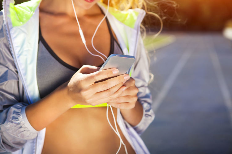 Midsection of woman holding mobile phone outdoors