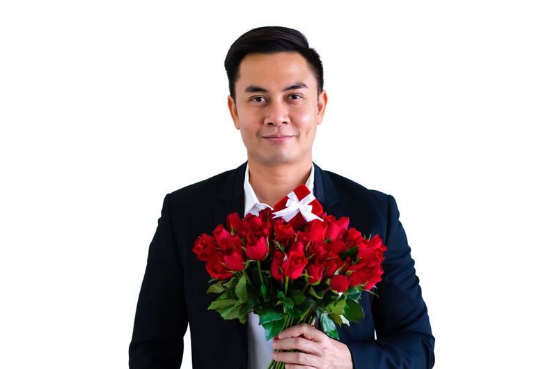 Portrait of young man holding red flower against white background