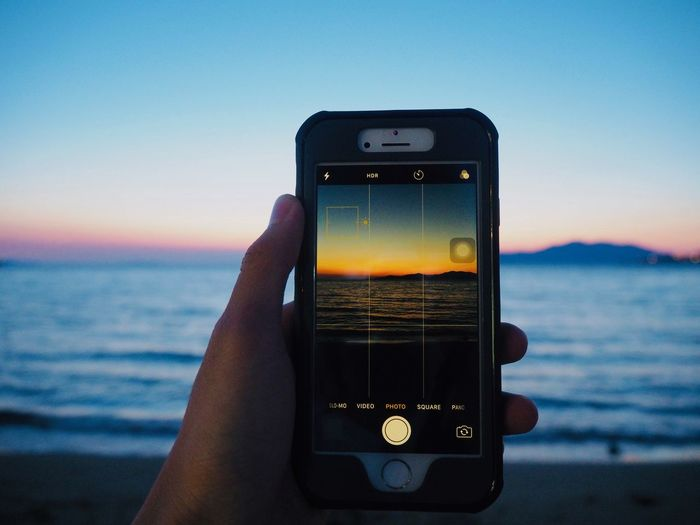 Hand holding smart phone against sea and sky