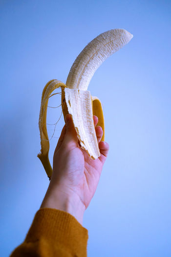 Close-up of hand holding banana against blue background