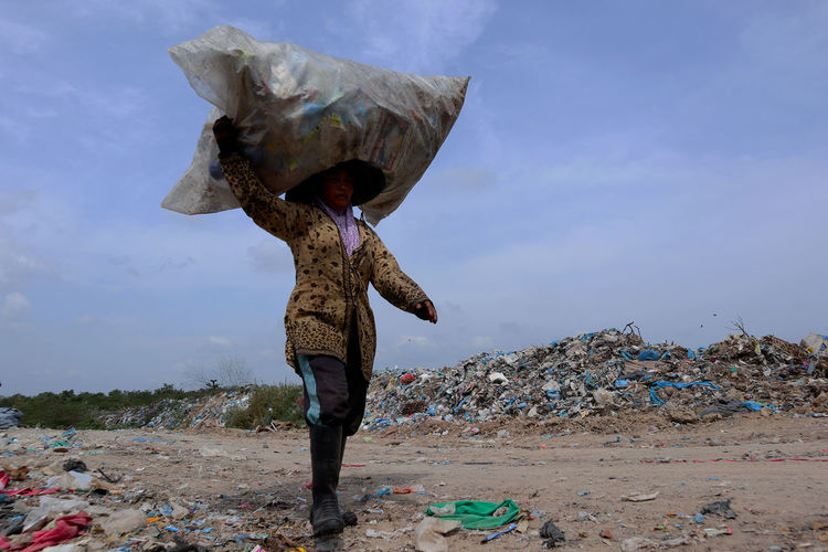 Low angle view of woman carrying garbage on head against sky