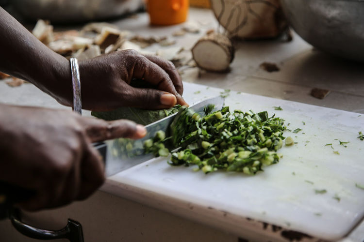 Cropped Image of Man Chopping Vegetable In Kitchen
