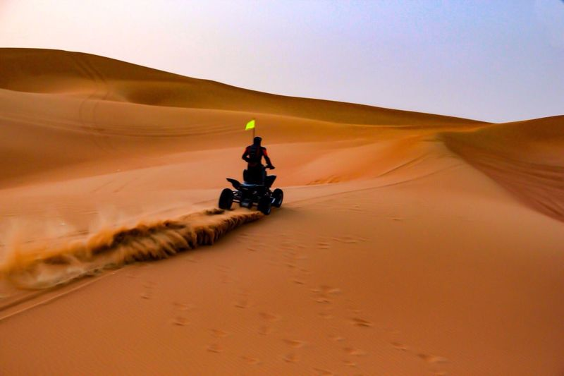 Rear view of man riding quadbike on sand at desert
