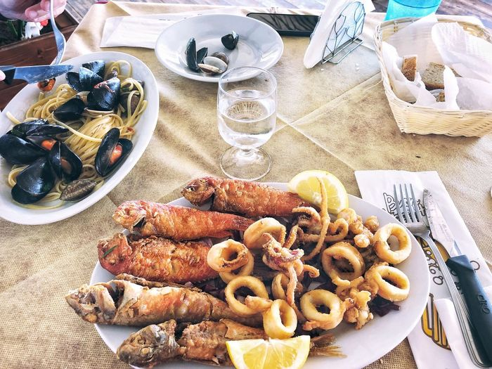 Lunch meal with linguini and mussels and seafood Italy Outdoors Food And Drink Food Freshness Table Glass Household Equipment Ready-to-eat High Angle View Refreshment Drink Drinking Glass Still Life Plate Seafood Day