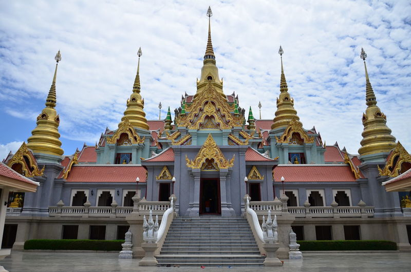 Low angle view of wat tang sai against cloudy sky