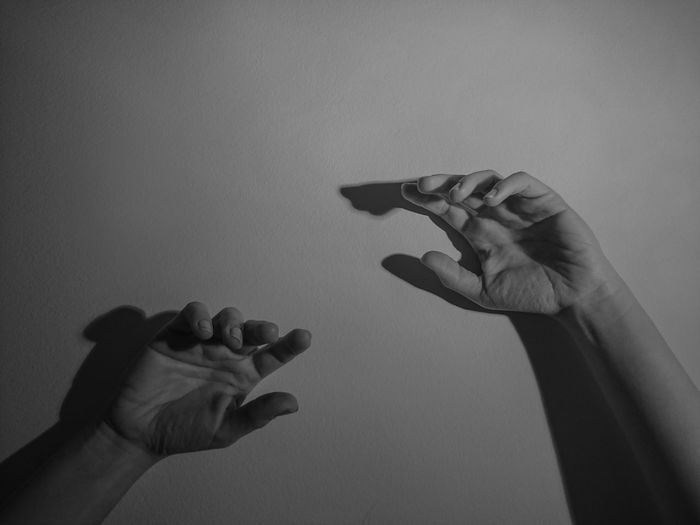 Cropped image of person hands against wall