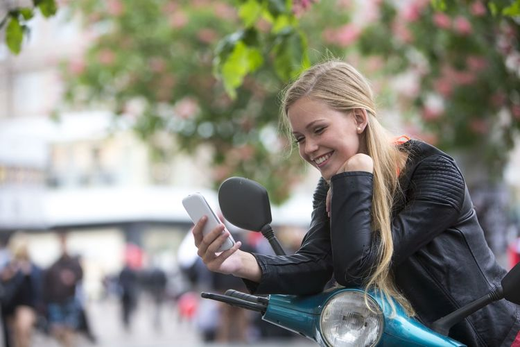 Smiling woman using mobile phone while leaning on motor scooter