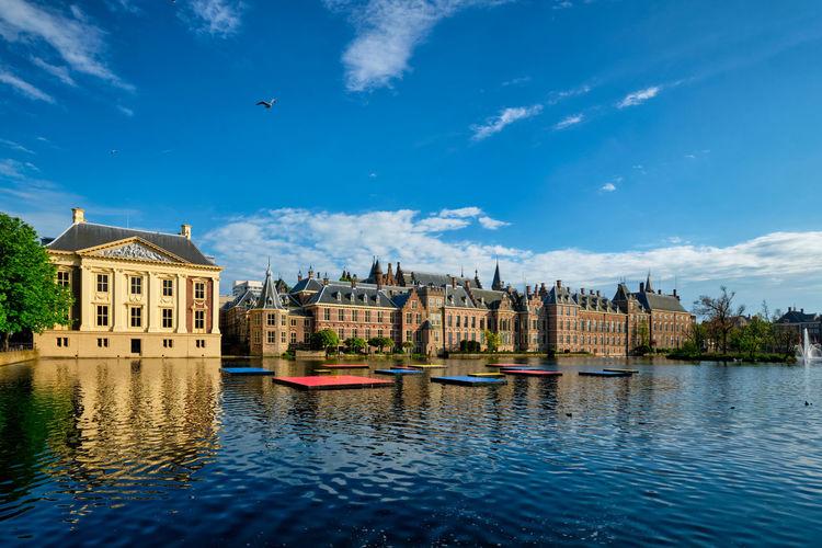 View of buildings by lake against sky