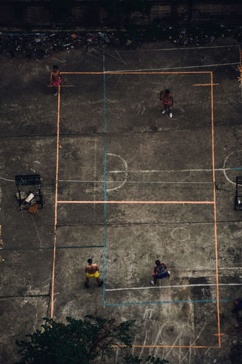 A group of young athletic men playing football in an ally in Bangkok, Thailand. People usually are seen playing football in their leisure time. The aerial view of the street shows a different side. High Angle View Group Of People Sport Architecture People Outdoors City Competition Aerial View Medium Group Of People Group Real People Athlete Leisure Activity Directly Above Streetphotography Match - Sport Rustic Style Aerial Landscape Birdeyeview Outdoor Games Games Volleyball Badminton Grunge