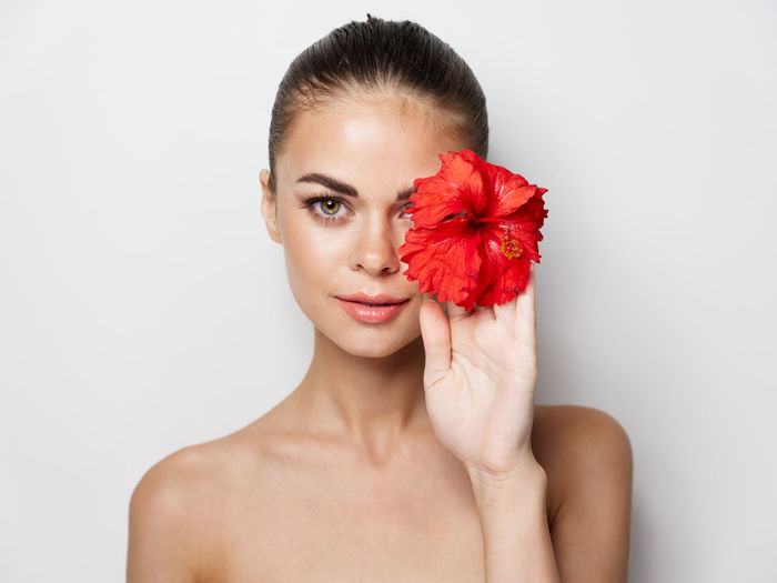 Portrait of woman holding flower over white background