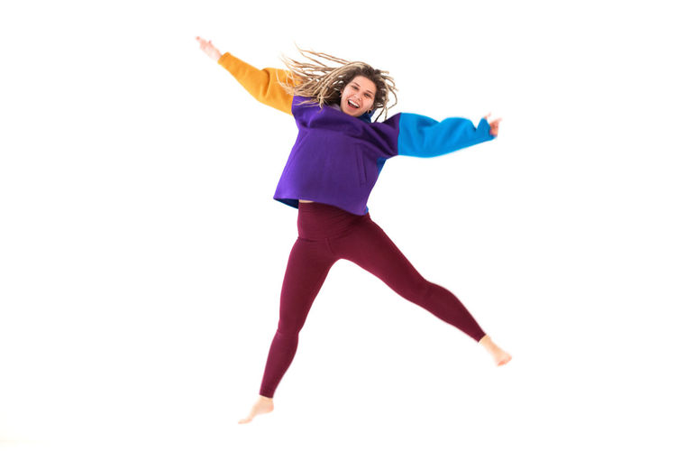 Full length of woman jumping against white background