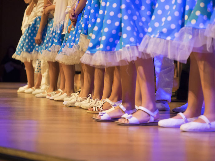 Low section of performers in blue skirt on stage