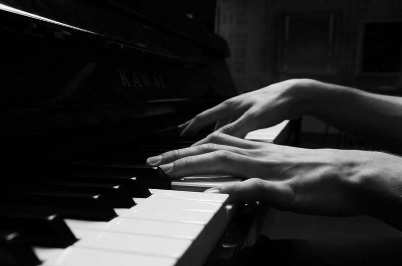 Cropped hands playing piano