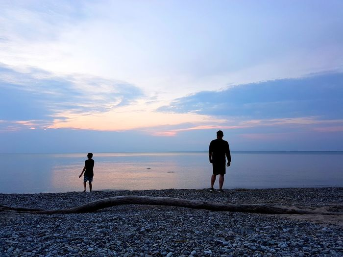 Rear Vie Of Father With Son Standing On Shore At Beach During Sunset