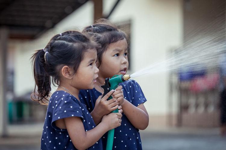 Siblings Spraying Water