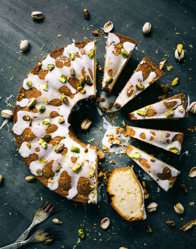 lemon pistachio cake cutted in slices on a dark backdrop   daylight foodphotography Cake Lemon Cake Pistachio Baked Foodphotography Food Photography Dessert Slices Dark Mood From Above  High Angle View Fork Light And Shadow No People Tasty Delicious Frosting Vegetarian Food