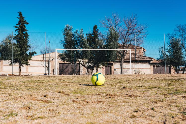 Soccer ball on field against clear blue sky