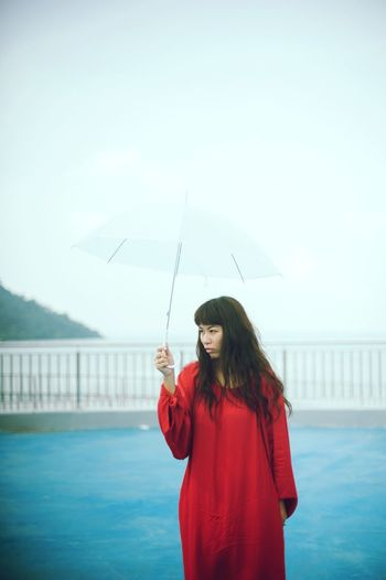Woman standing in red boat against sky