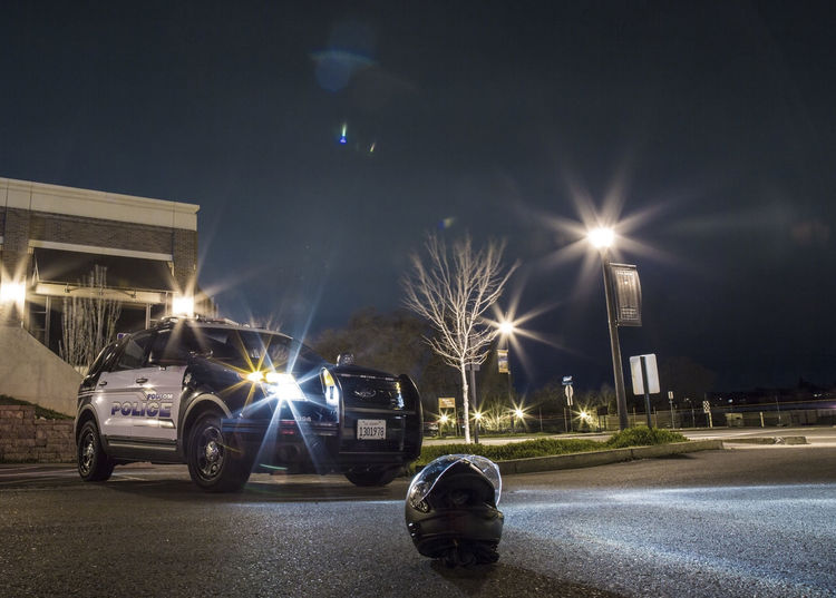 Police car halting motorcyclist Architecture Building Exterior Built Structure Car City Illuminated Land Vehicle Lens Flare Light Beam Light Trail Long Exposure Mode Of Transport Night No People Outdoors Police Car Police Cars Road Sky Tranquility Transportation Tree First Eyeem Photo