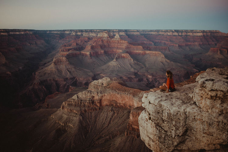 Side view of woman sitting on cliff at grand canyon