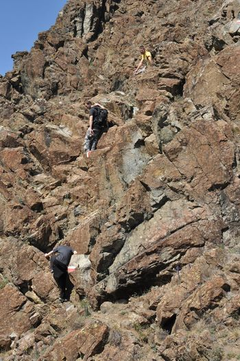 Rear view of men climbing on rock