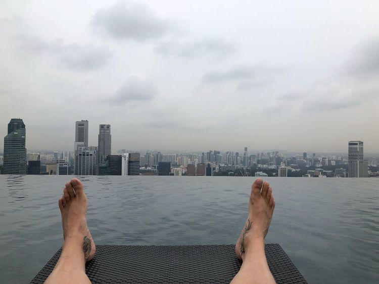 Relaxing at the Pool EyeEm Selects Architecture Built Structure Building Exterior Sky Low Section City Cloud - Sky Human Body Part Water Human Leg One Person Real People Personal Perspective barefoot Nature Building Body Part Leisure Activity Lifestyles Limb