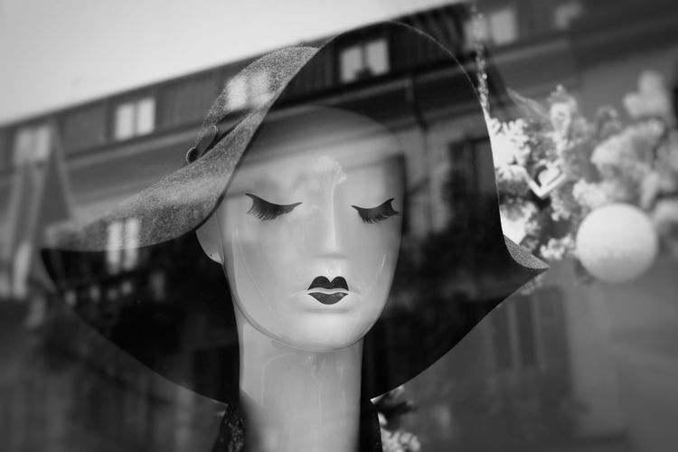 Close-up of mannequin seen through display window