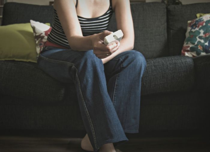 Midsection of woman holding remote control while sitting on sofa at home