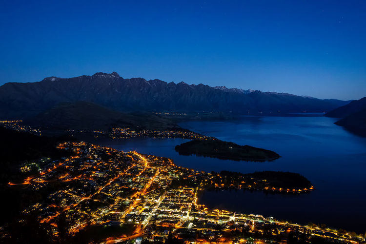 Scenic view from high POV of Queenstown, Lake Wakatipu and The Remarkable mountain range during sunset Architecture Astronomy Blue Business Finance And Industry City Cityscape Harbor Illuminated Landscape Mountain Night No People Outdoors Premiere Sea Sky Travel Travel Destinations Vacations Water