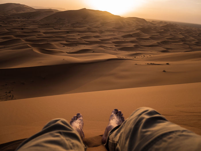 Low section of man sitting on desert