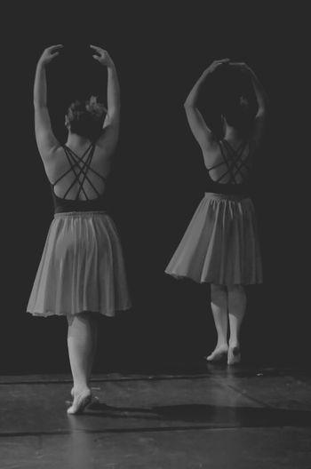 Full length of female ballerinas against black background