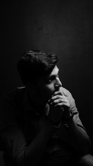 Young man looking away against black background