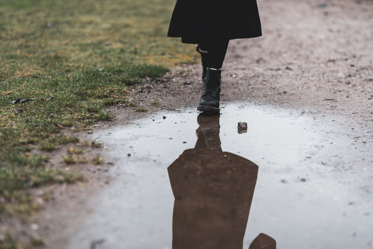 Low section of woman standing on puddle during rainy season
