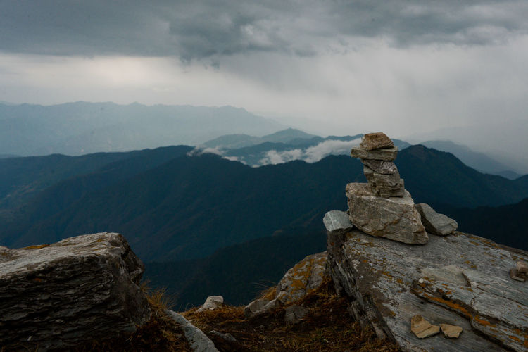 Stack of rocks on mountain against cloudy sky