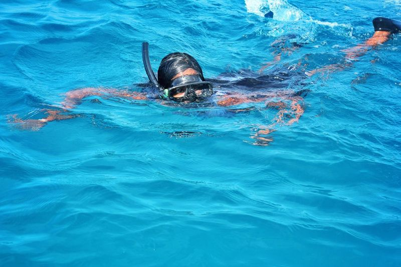 High angle view of teenage girl swimming in sea