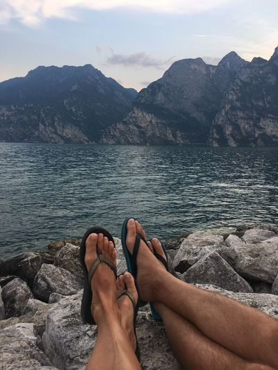 Low Section Of Couple Relaxing On Rock At Lakeshore Against Mountains