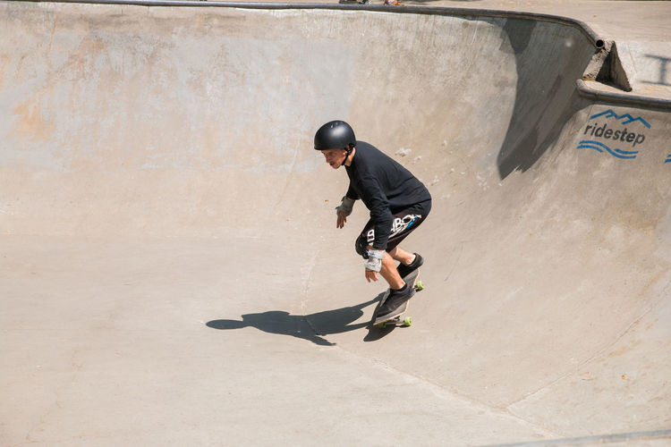 man skateboarding in a skatepark Full Length One Person Men Skateboard Park Skill  Sport Shadow Lifestyles Leisure Activity Day Motion Sunlight Real People Architecture Casual Clothing Sports Equipment Skateboard Vitality Outdoors Concrete Effort