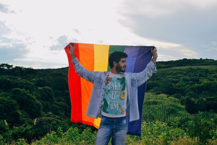 Man holding rainbow flag against sky
