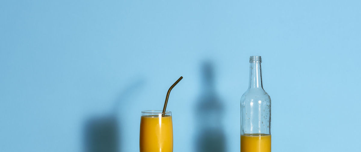 Glass of orange juice and empty bottle on blue background. orange juice in a glass and metal straw.