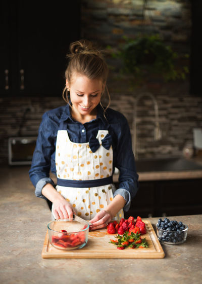 Blond Hair Blueberries Childhood Day Domestic Life Domestic Room Focus On Foreground Food Food And Drink Freshness Front View Fruit Girls Healthy Eating Indoors  One Person People Preparation  Real People Smiling Strawberries